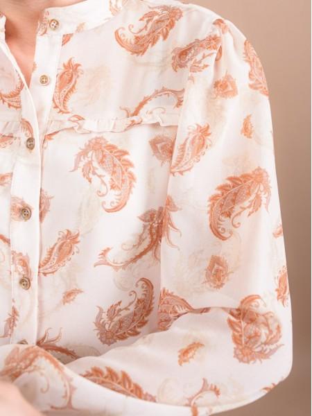 Εμπριμέ μπεζ μακρυμάνικο ημιδιαφανές πουκάμισο με λαχούρια, στρογγυλή λαιμόκοψη, πιέτες στους ώμους, μικρά βολάν μπροστά και λάστιχο στο τελείωμα στις μανσέτες Enzzo