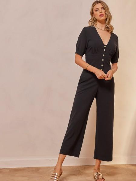 Μαύρη κοντομάνικη cropped ολόσωμη φόρμα, με ξύλινα κουμπιά μπροστά, μικρές σούρες στα μανίκια, στο μπούστο και στην πλάτη, σταθερή μπάσκα στην μέση και πλαϊνές τσέπες Enzzo