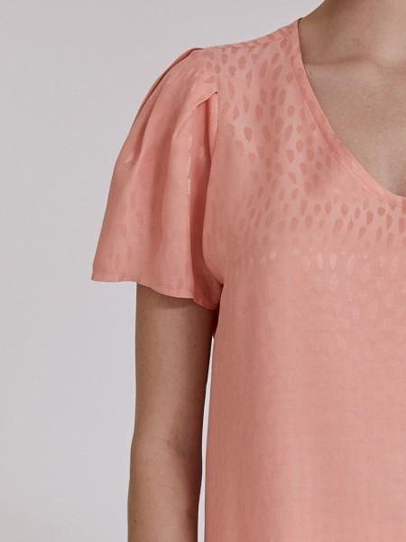 Βερυκοκί κοντομάνικη μπλούζα σε μονόχρωμο ανάγλυφο ύφασμα, με V-λαιμόκοψη, πιέτες στους ώμους, κουφόπιετες στην πλάτη, ασυμμετρία στο τελείωμα και αποσπώμενο κολιέ Vener