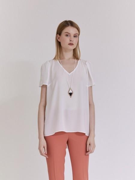 Εκρού κοντομάνικη μουσελίνα μπλούζα με V-λαιμόκοψη, πιέτες στους ώμους, κουφόπιετες στην πλάτη, ασυμμετρία στο τελείωμα και αποσπώμενο κολιέ Vener